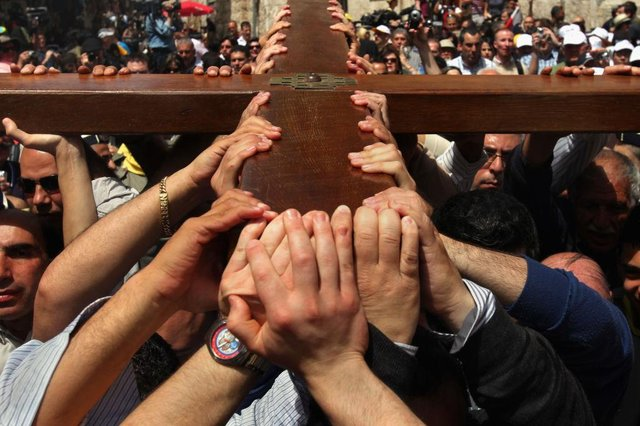 Christians in Jerusalem carry their large wooden cross along the route tradition says Jesus carried the cross on, to mark Good Friday
