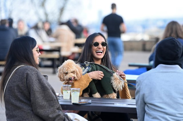 People enjoy a drink outside Alexandra Palace in London yesterday after lockdown restrictions in England were relaxed (Picture: Kate Green/Getty Images)