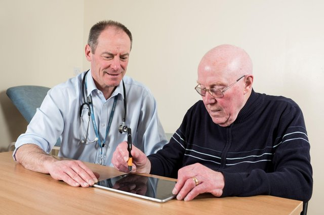 Prof Richard Walker, clinical lead adviser to Edinburgh-based Manus Neurodynamica, pictured with a patient, prior to Covid measures.