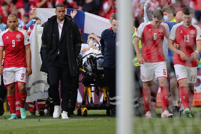 Denmark's players escort midfielder Christian Eriksen as he is evacuated after collapsing on the pitch during the EURO 2020 Group B match between Denmark and Finland.