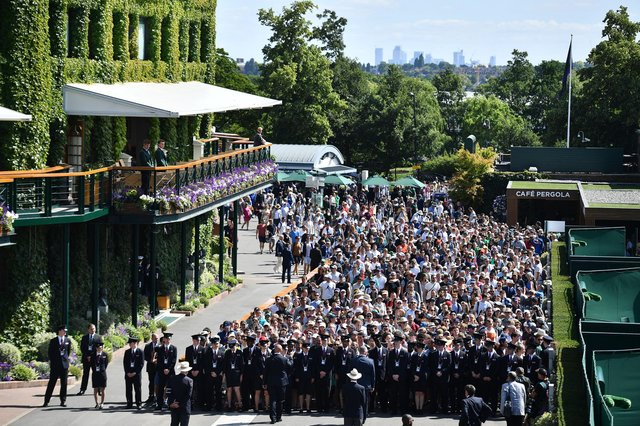 Spectators queue to enter the All England Tennis Club on the first day of the 2019 Wimbledon Championships.