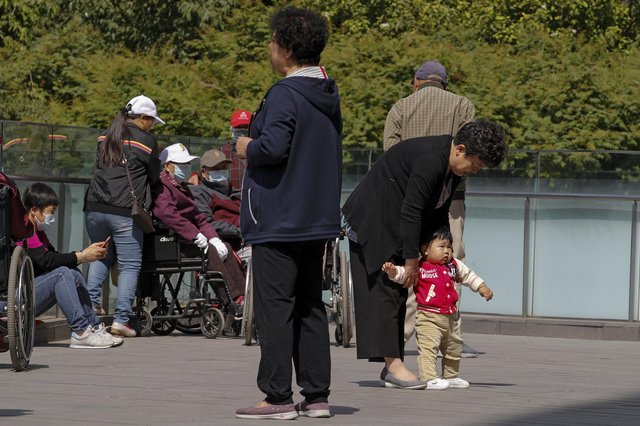 China's ruling Communist Party will ease birth limits to allow all couples to have three children instead of two to cope with the rapid rise in the average age of its population. (AP Photo/Andy Wong)