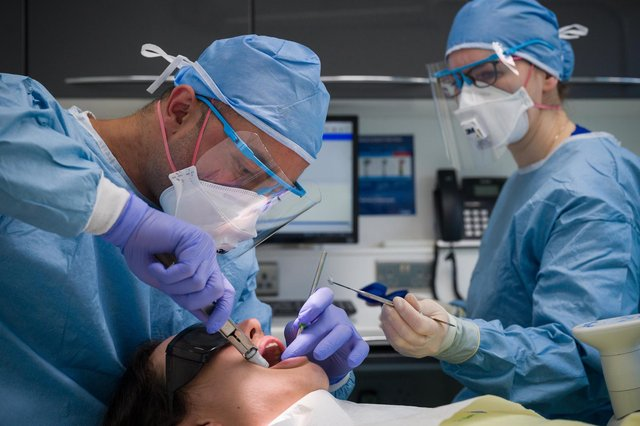 Dentist Fiez Mugha and Dental Nurse Johanna Bartha carry out a procedure on a patient. Photo by Leon Neal/Getty Images