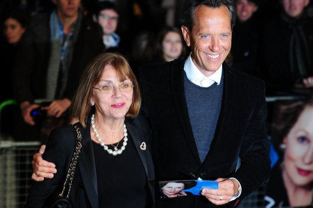 """(FILE PHOTO) Actor Richard E Grant has paid tribute to his wife of 35 years Joan Washington in a heartfelt message on social media after she reportedly died last night. British actor Richard E Grant (R) poses with his wife Joan Washington (L) on the blue carpet as she arrives to attend the European premiere of the film """"The Iron Lady"""" at BFI Southbank in London on January 4, 2012. The biopic set in the present day is a story of ambition; power won and power lost; and also love, with flashes of memory whisking the viewer off to a time when Margaret Thatcher, played by Meryl Streep, was the Western world's first female leader and possibly Britain's most divisive prime minister.   AFP PHOTO / LEON NEAL (Photo credit should read LEON NEAL/AFP via Getty Images)"""