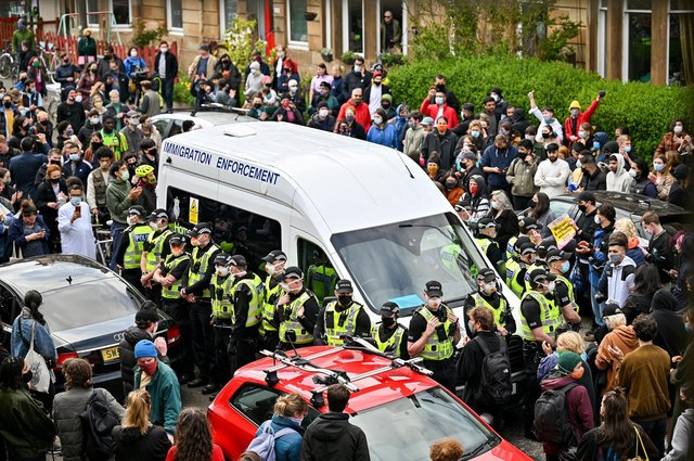 Protesters block a UK Home Office van to stop it from leaving Kenmure Street in Glasgow (Picture: Jeff J Mitchell/Getty Images)