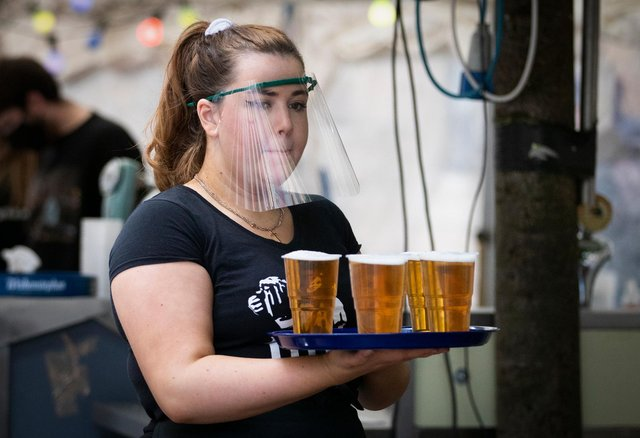 A member of staff serves drinks in the beer garden at the Bier Halle in Glasgow during the lockdown easing last summer.