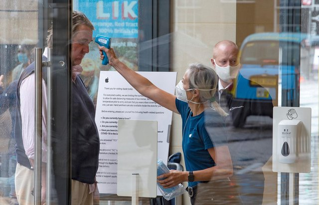 A retail worker  takes the temperature of a customer entering the Apple Store on Princes Street in Edinburgh on June 29, 2020