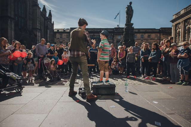 Huge crowds traditionally flock to Edinburgh city centre for free street theatre performances in August. Picture: David Monteith Hodge