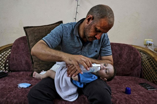 Mohammad al-Hadidi feeds his son Omar, who was pulled alive from the rubble of a building destroyed by an Israeli airstrike on the Shati refugee camp. All his other children, Suhayb, 13, Yahya, 11, Abderrahman, eight, and Osama, six, and their mother Maha Abu Hattab, 36, were killed, (Picture: Mahmud Hams/AFP via Getty Images)