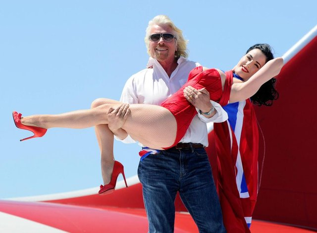 Founder and President of Virgin Group Sir Richard Branson holds burlesque artist Dita Von Teese as they appear on the wing of a Virgin Atlantic Airways 747-400 aircraft in 2010 (Photo: Ethan Miller/Getty Images)