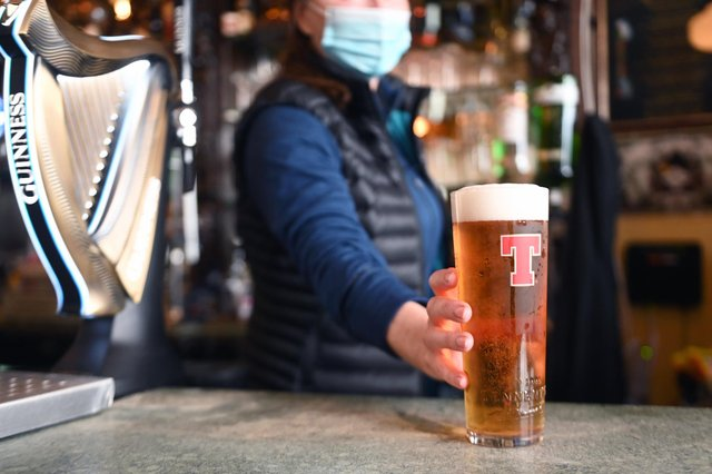 A bar person serves up a pint of Tennants lager. Picture: John Devlin