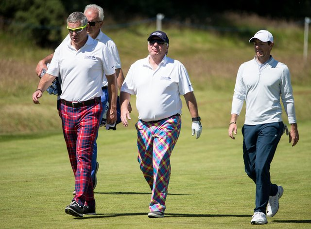 Former Scottish rugby Gavin Hastings, Aberdeen Asset Management chief executive Martin Gilbert with Ireland's Rory McIlroy make their way to the 15th