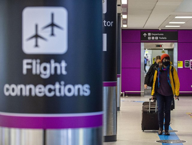 Travellers arrive at Edinburgh Airport wearing face masks. Picture: Lisa Ferguson