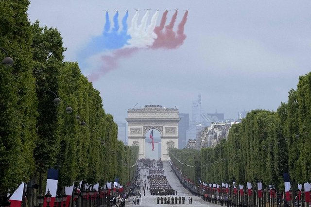 Alphajet aircraft fly over L'Arc de Triomphe during the annual Bastille Day military parade on the Champs-Elysees avenue in Paris on 14 July 2021 (Getty Images)