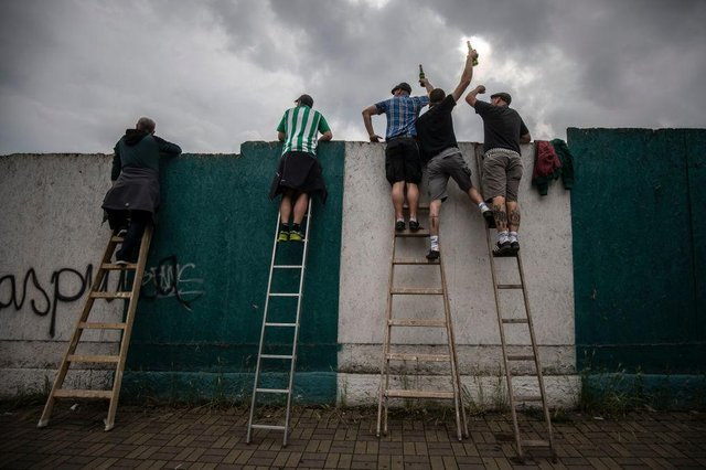 Football fans have been using ladders to get a glimpse of their team. Picture: Gabriel Kuchta/Getty Images