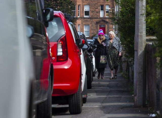 Pedestrians struggling to get past cars parked on an Edinburgh pavement. Picture: Lisa Ferguson