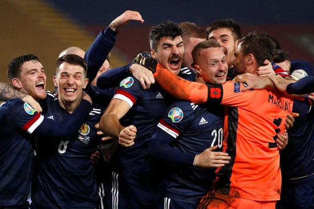 David Marshall (in orange) is mobbed by his Scotland team-mates after his penalty save in the shoot-out against Serbia ensured Scotland's qualification for Euro 2020, which will be played this summer. Picture: Srdjan Stevanovic/Getty Images