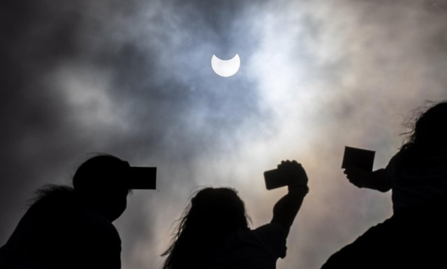 Partial solar eclipse watched by people through welders glass on Arthur's Seat in Edinburgh picture: Katielee Arrowsmith SWNS