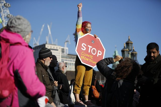 A climate change activist gets her message across during a protest in London