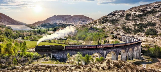 The Jacobite steam train travelling across the Glenfinnan Viaduct.