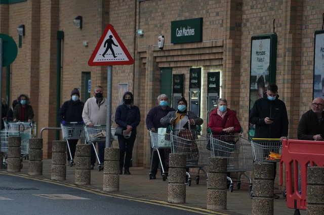 People queue outside a Morrisons supermarket in Whitley Bay, Tyne and Wear.