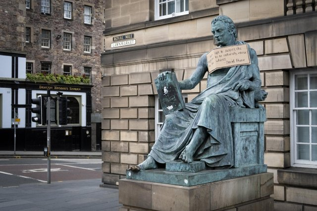A sign hangs from the statue of the 18th-century philosopher David Hume on Edinburgh's Royal Mile with a racist quote from his essay Of National Characters (Picture: Jane Barlow/PA)